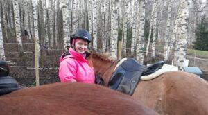Nainen hevosten kanssa pihalla