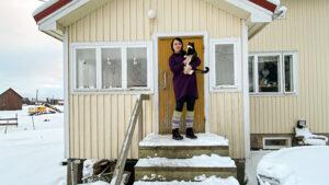 Nainen seisoo omakotitalon portailla kissa sylissään.