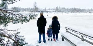 Isovanhemmat ja lapsenlapsi talvisen joen rannassa.