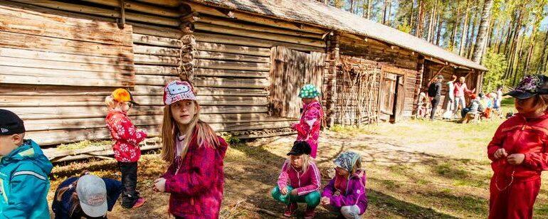 Lapsia kevään luokkaretkellä taustallaan Laurinmäen pitkä karjasuoja, eli liiteri, navetta ja talli.
