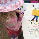 Pieni tyttö leikkaa saksilla taidetyöpajassa.
