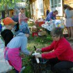 Ohjaja neuvoo lapsia valmistamaan puumiekkaa Keltaisen talon pihamaalla kesätapahtumassa.
