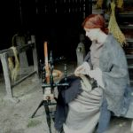 Torppariasuun pukeutunut nainen kehrää rukilla lankaa.