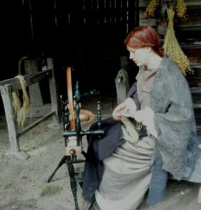 Crofter woman is making yarn using the spinning wheel at Laurinmäki Crofter's museum