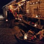 Laurinmäen joulunavauksen myyntipöytiä pitkän karjarakennuksen seinustalla.