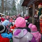 Esiintyjä Katti Matikainen tervehtii runsasta lasten yleisöä Vähä-Kurjen torpan kuistilla Laurinmäen joulunavauksessa.
