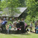 Kesänavaus tapahtumassa joukko kaikenikäistä yleisöä osallistuu linnunpönttöjen rakentamiseen keskellä museon pihaa.