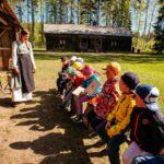 Luokkaretkellä olevat lapset kuuntelevat torpparin asuun pukeutunutta opasta torparimuseon pihamaalla.