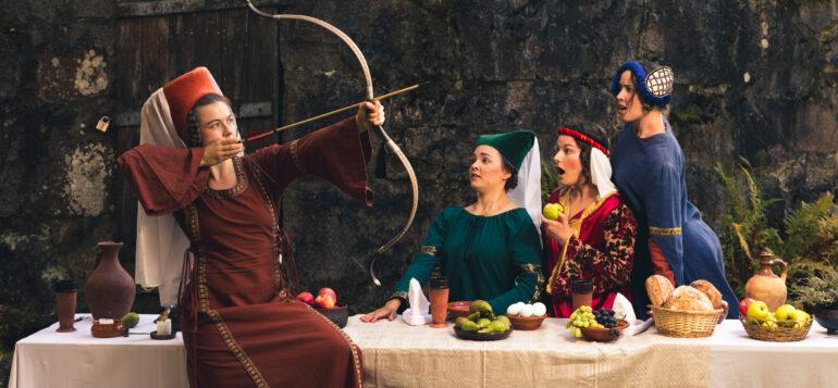 Säilättäret ryhmä on pukeutunut keskiaikaisiin asuihin ja yksi neljästä pöydän ääressä istuvasta naisesta virittää joustaan