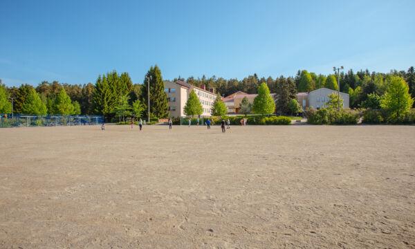Hiekkakenttä, jossa lapsia pelaamassa.
