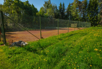 Tenniskenttä aurinkoisena kesäpäivänä.