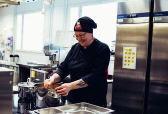 Ateriapalveluiden työntekijä valmistamassa ruokaa keskuskeittiö Tuuvingissa.