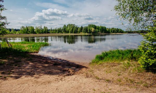 Aurinkoisena päivänä kuvattu järven hiekkaranta Rantalahdessa.
