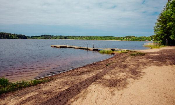 Suruttoman hiekkaranta Alasjärven rannalla aurinkoisena kesäpäivänä.