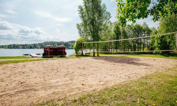 Lentopalloverkko Valajärven hiekkarannalla, taustalla järvimaisema.