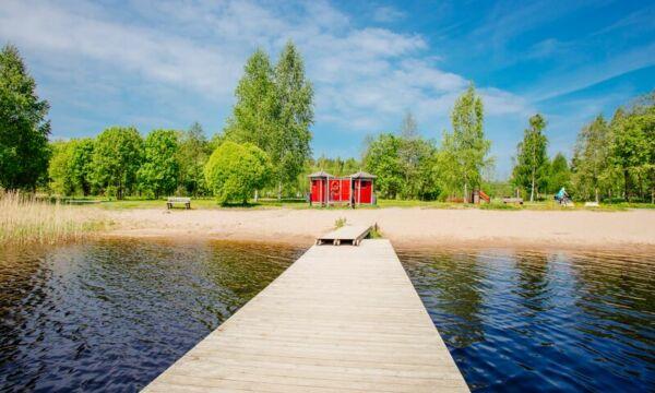 Tietyn uimaranta Tervakoskella kesäpäivänä laiturilta kuvattuna. Rannalla punainen pukukoppi.