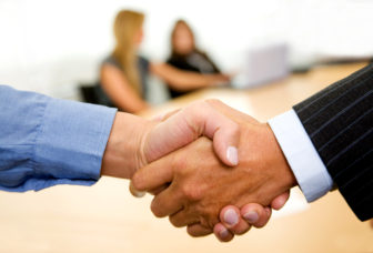 business handshake in an office with team behind