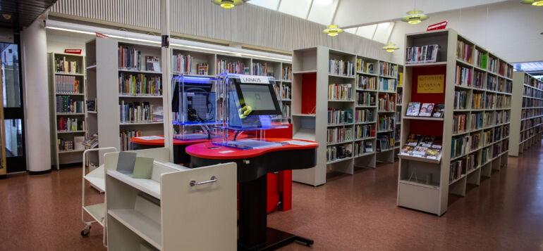Kirjaston puna-mustat lainausautomaatit.