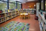 Kirjaston lasten kuvakirjaosasto, pyöreä lukupöytä tuoleineen ja lattialla värikäs liikennematto.