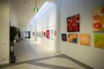 Pääkirjaston pitkänomainen näyttelytila ja taululla kauniita maalauksia.