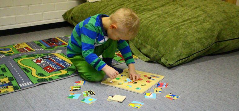 Lapsi kokoaa keskittyneenä palapeliä toimintaterapiatilassa.