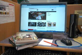 Tietokoneella auki verkkokirjasto ja pöydällä pino kirjoja.