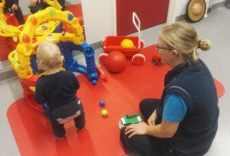 Lapsi ja fysioterapeutti leikkimatolla leikkimässä.
