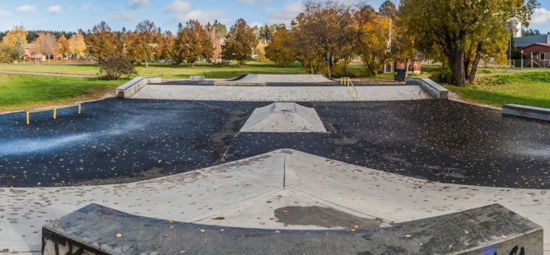 Skatepark ramppeja puiston keskellä.