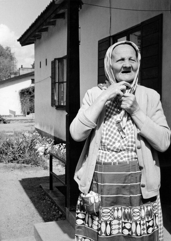 Vanha mummo sitoo huiviaan eläkeläisasuntojen edessä.