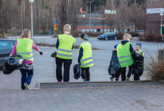 Nuoria Kui Siistii! talkoissa menossa keräämään roskia jätesäkkien kansssa huomioliivit päällä.