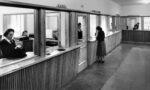 Konttorin aulasta otettu kuva vuodelta 1949. Kassaluukulla työskentelee nainen kassakoneen ääressä, huoltoluukulla asioi toinen nainen.