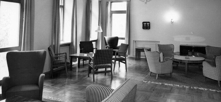 Vanha kuva virkailikerhon sisätiloista. pöytä - ja sohvaryhmineen.