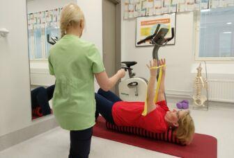 Fysioterapeutti ohjaa asiakkaalle kuminauhaharjoitusta valoisassa terapiatilassa.