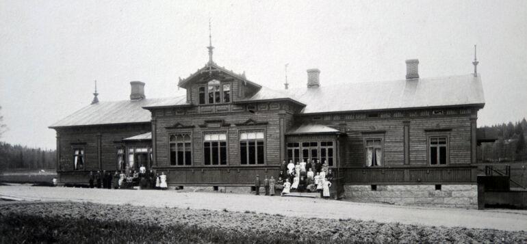 Vanha kuva koristeellisesta, puisesta kansakoulusta, jonka edessä seisoo lapsia ja aikuisia.