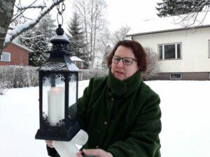 Jutta laittaa kynttilöitä lyhtyihin talvisella kotipihallaan.