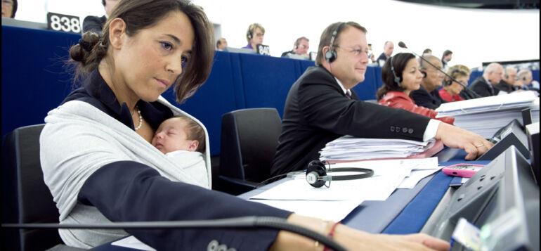 Europarlamentin jäsen painaa äänestysnappia vauva sylissään.