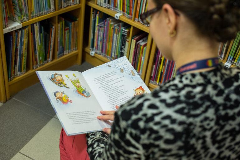 Kirjaston työntekijä lukee kuvakirjaa, jonka aukeamalla lasketaan mäkeä.