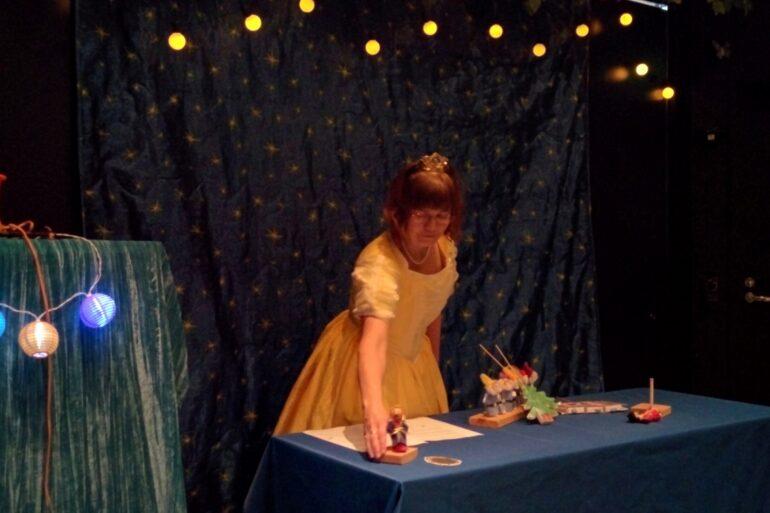 Nukketeatteriesitys, jossa pöydällä pieniä nukkeja ja hämärä valaistus. Esiintyjällä keltainen prinsessamekko ja kruunu.