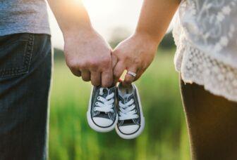 Pariskunta kläsikädessä pidellen vauvan kenkiä