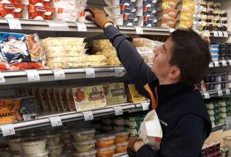 Työntekijä avotyössä kaupassa hyllyttämässä tavaroita.