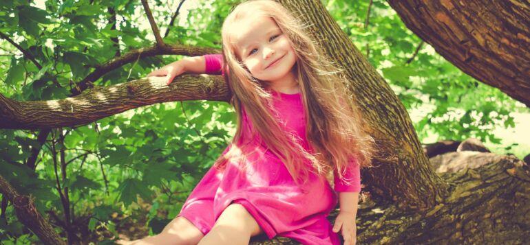Tyttö istuu vaahterapuun oksalla.