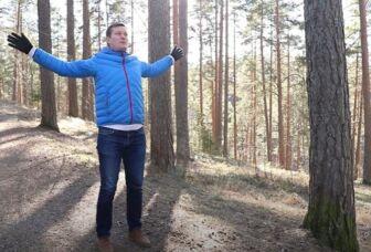 Mies tekee pihajumppaliikkeitä metsässä.