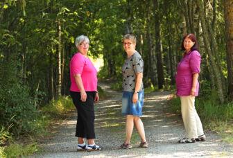 Kolme naista kävelyllä metsäisellä tiellä.