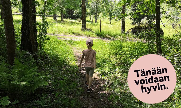 Tänään voidaan hyvin. Tyttö kävelee kesäistä metsäpolkua.
