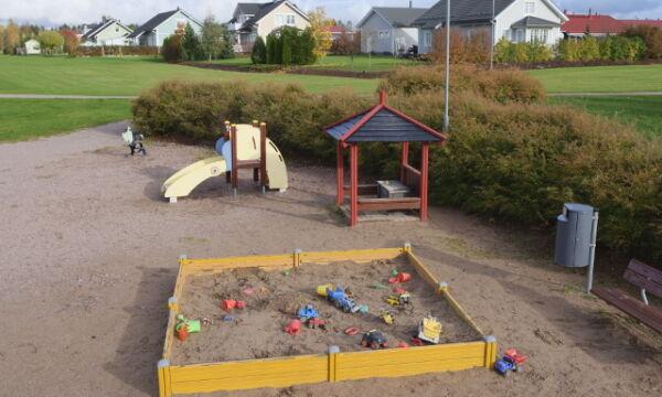 Harvialan leikkipaikan hiekkalaatikko, pienten keinu ja katos.