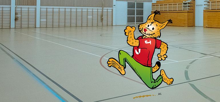 Janakkalan piirretty maskotti-ilves juoksee Turengin liikuntahallin salissa.