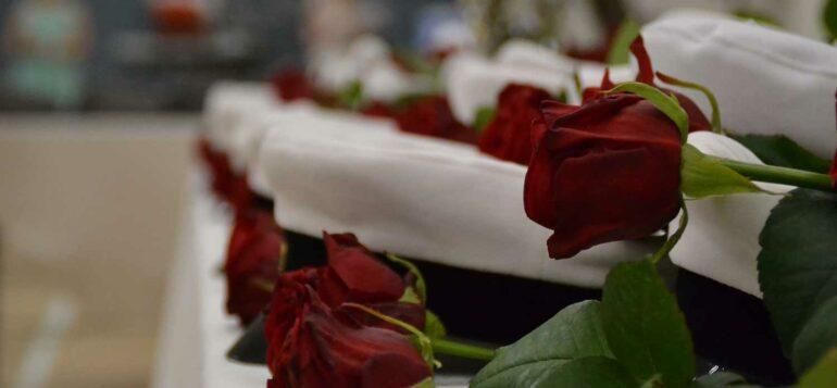 Ylioppilaslakit ja -ruusut rivissä odottamassa juhlijoita.