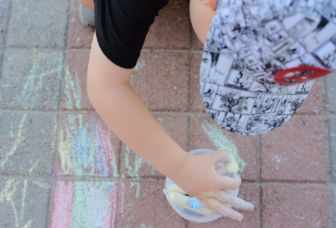 Lapsi taiteilemassa katuliiduilla kivetykselle päiväkodin pihassa.