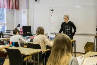 Opettaja opetamassa luokan edessä.