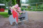 Kaksi tyttöä kiikkumassa jousikeinussa Haltian päiväkodin pihassa.